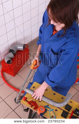 Female plumber sawing pipe