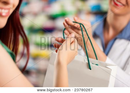 Female pharmacist with a female customer in her pharmacy