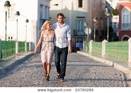 Couple having a city break in summer walking on a bridge over a river in the evening light