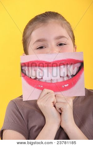 Girl holding an enlarged picture of her teeth in front of her mouth