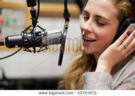 Close up of a singer recording a track in a studio