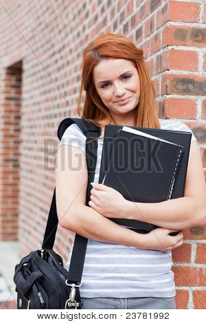 Portrait of a smiling student holding her binder while looking at the camera