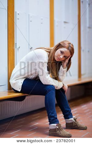 Portrait of a sad student sitting on a bench looking at the camera
