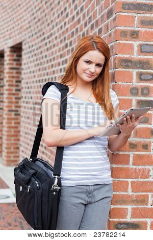 Portrait of a serious student holding a tablet computer outside a building