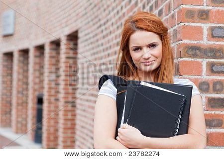 Serious student holding her binder while looking at the camera