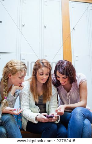 Portrait of a student showing a text message to her friends in a cloakroom