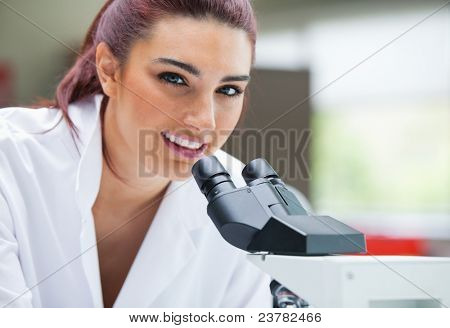 Close up of a scientist posing with a microscope in a laboratory