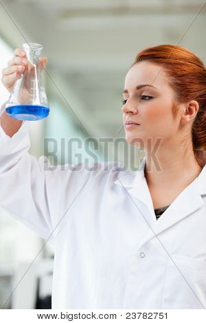 Portrait of a scientist looking at a blue liquid in an Erlenmeyer flask
