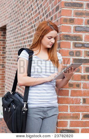 Portrait of a serious student working with a tablet computer outside a building