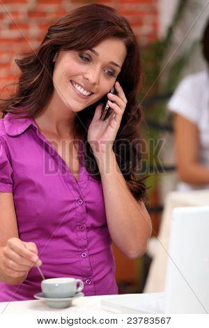 Woman on a cellphone while stirring an expresso in a restaurant
