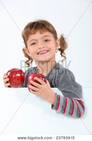 little girl holding two apples