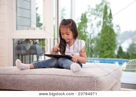 Happy young child playing with a digital tablet in an indoor setting