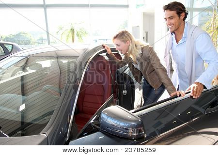 Couple looking inside new car
