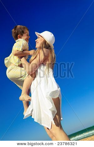 Boy is on his mother's hands at beach