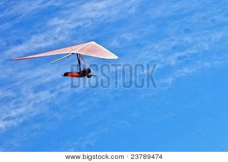 Hangglider flying on a wing in a blue sky