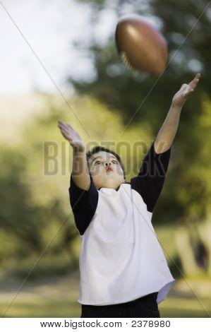 Garoto pegando uma bola de futebol