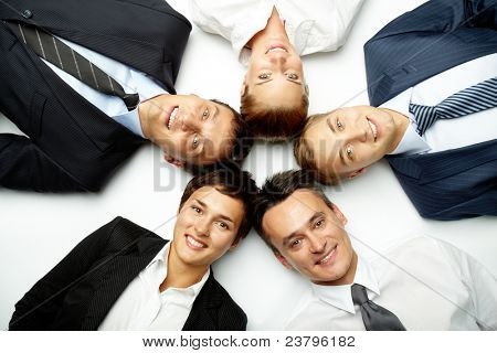 Five business people lying in floor, looking at camera and smiling
