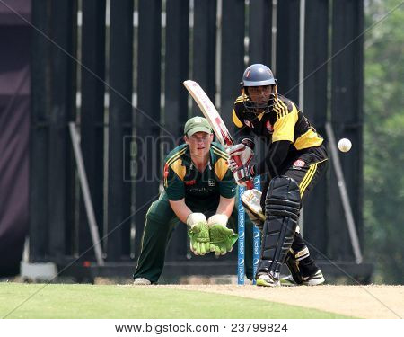 PUCHONG, MALAYSIA - SEPT 24: Guernsey's wicketkeeper Tom Kimber eyes Malaysia's Ahmad Faiz bats in this Pepsi ICC WCL Div 6 finals at the Kinrara Oval on September 24, 2011 in Puchong, Malaysia.
