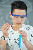 Handsome Asian Teenager Wearing Safety Goggles Using Test Tube And Pipette While Carrying Out Experi poster