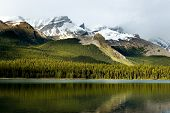 stock photo of mountain-range  - Rockies mountain range reflecting in Maligne lake Jasper national park - JPG