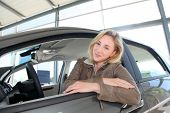 Woman sitting in brand new car poster