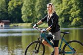Mountain Biking Young Woman Standing By Lake