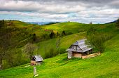 Woodshed On A Grassy Hillside On A Cloudy Day. Village Outskirts With Rural Fields In Mountainous Ar poster