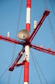 Satellite Dishes And Antennas On The Red-white Telecommunication Tower Against Blue Sky. poster