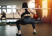 Athletic Girl Sit Ups With Barbell. Female Successfully Practices Workout. Blurred Background And Yo poster
