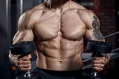 Athlete Muscular Bodybuilder  With Dumbbells .fitness Concept Background. poster