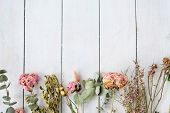 Dried Shabby Chic Flowers And Twigs On White Wooden Background. Free Space Concept poster