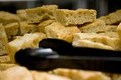 foto of flat-bread  - Foccacio specialty bread cut into squares with black tongs - JPG