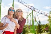 Two affectionate girls in sunglasses looking at one of amusements while spending time in theme park  poster