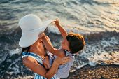 Cute Top View Of Young Mother Playing With Daughter With White Hat At The Sea Background. Family Vac poster