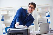 Businessman angry at copying machine jamming papers poster