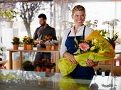 picture of flower shop  - Female sales assistant working as florist and holding bouquet with customer in background - JPG
