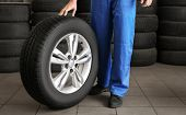 Mechanic with car wheel in repair shop. Tire service poster