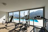 Gym overlooking the pool and hills. Nobody inside poster