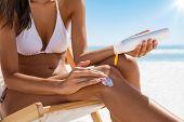 Closeup of woman applying suntan lotion on leg. Closeup of woman hand applying sunscreen cream while poster