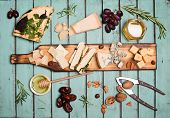 Cheese Selection On Wooden Rustic Board. Cheese Platter With Different Cheeses, Grapes, Nuts, Honey  poster