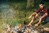 Lone Wanderer Camping In Woods. Serious Bearded Man Frying Sausages Over Fire. Barefoot Hipster Sitt poster