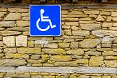 Traffic Sign Indicating Parking For Persons With Disabilities Hanging On Rough Stone Wall, Disabled  poster