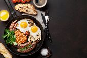 English breakfast. Fried eggs, sausages, bacon, beans, toasts, tomatoes, orange juice and coffee cup poster