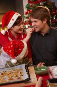 foto of nuclear family  - Smiling wife handing christmas cake to father to taste - JPG