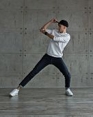 Teenager Guy In Baseball Cap And Sneakers, Jeans And White Sweater Dancing Hip-hop. Dynamics Of Mode poster