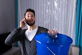 Worried Young Man Calling Plumber While Leakage Water Falling Into Bucket At Home poster