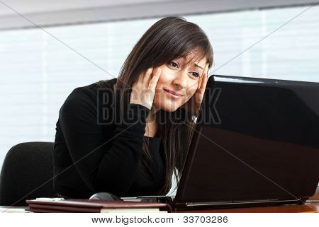 Businesswoman getting depressed in front of her laptop