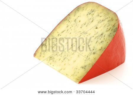 piece of traditional frisian cheese with herbs on a white background