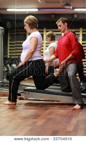 Physical therapist stretching ,pregnant woman's leg in gym