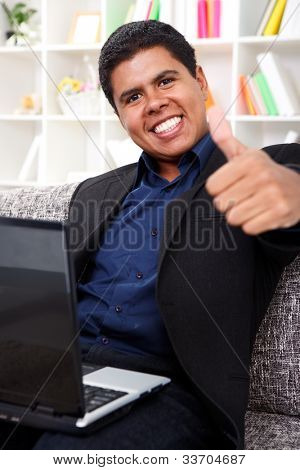 success businessman working on laptop and showing thumbs up